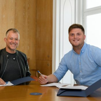 David Nicol Williams, CEO of NomadX (L), and Radim Rezek, CEO of Flatio, signing a merger deal (Photo credit: NomadX/LinkedIn)